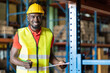 Leinwandbild Motiv African American smiling male warehouse worker in safety vest and helmet with clipboard working and checking products or parcel goods on shelf pallet in industrial storage warehouse