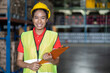 Leinwandbild Motiv Portrait of African American smiling female warehouse worker with clipboard working and checking products or parcel goods on shelf pallet in industrial storage warehouse