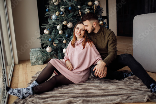 Foto Adorable couple sit near the Christmas tree at home, smiling, charming husband h