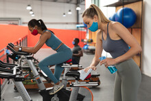 Fit Caucasian Woman Wearing Face Mask Sanitizing Seat Of Stationary Bike Before Working Out In The G