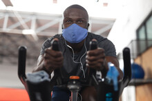 Fit Man African American Wearing Face Mask And Earphones Exercising On Stationary Bike In The Gym