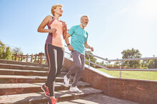 Energize Your Morning. Full Length Shot Of Active Mature Family Couple In Sportswear Running Together In The Park On A Sunny Morning. Joyful Senior Couple Working Out Outdoors