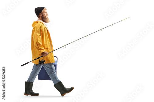 Obraz Full length profile shot of a bearded fisherman walking and carrying a fridge and a fishing rod - fototapety do salonu
