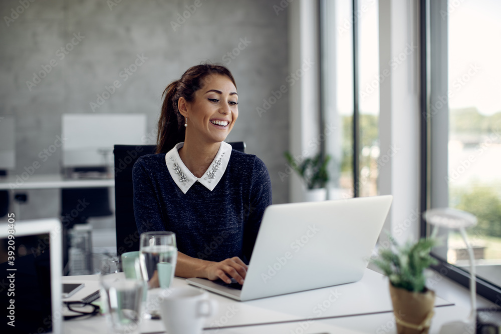 Fototapeta Young happy businesswoman working on laptop in the office.