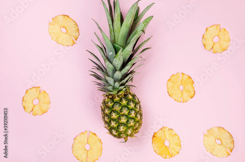 Pineapple with dried pineapple wedges around. Fototapet