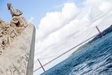 Monumento A Los Descubrimientos O Padrao Dos Descobrimentos Y Puente Del 25 De Abril O Ponte 25 De Abril En La Ciudad De Lisboa, Pais De Portugal