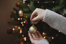 Decorating Christmas Tree With Modern Golden Bauble In Festive Decorated Room With Lights