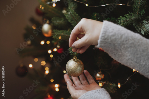 Obraz Decorating christmas tree with modern golden bauble in festive decorated room with lights - fototapety do salonu