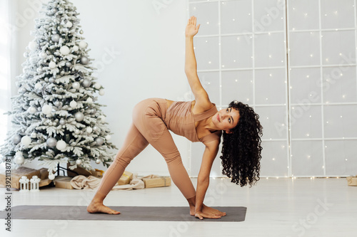 Beautiful flexible young woman is doing stretching exercise near decorated fashi Canvas