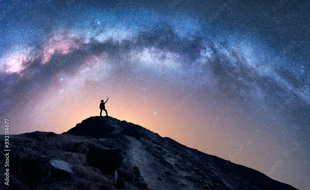 Fototapeta Arched Milky Way and happy man on the mountain at night. Silhouette of guy with raised up arm on the hill, sky with stars, yellow light in Nepal. Galaxy. Space landscape with milky way arch. Travel