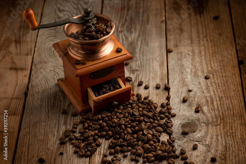 Foto Coffee grinder with coffee beans over wood