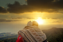 Couple Of Friends Enjoying Sunset On The Top Of The Mountain. Lovely Travelling Couple Looking At The Sunset During Road Trip. Concept About Lifestyle, People, Travel And Love.