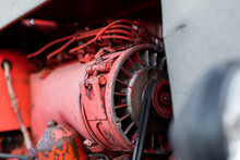 Closeup Of Four Cylinder Diesel Tractor Engine With Visible Belt Rusty Tracks Hydraulic Parts And Wiring Red Paint In Sunny Autumn Day