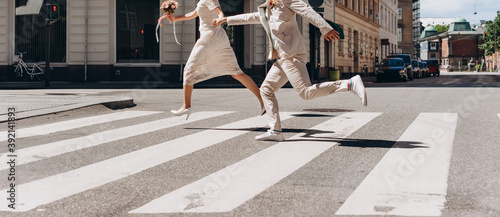 Photo Bridal couple running across the street in Copenhagen