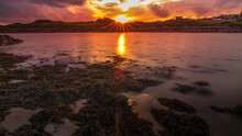 Isle Of Whithorn Harbour Set In A Dramatic Sunset, Still Water And Sunburst