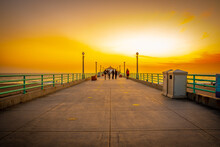 Manhattan Beach Pier At Sunset In California. People Take Pictures, Stroll, Enjoy The Beach. Famous American West Coast Location For Tourists And Locals.