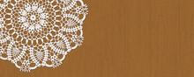 白いレース編みを、茶色のテーブルに飾る