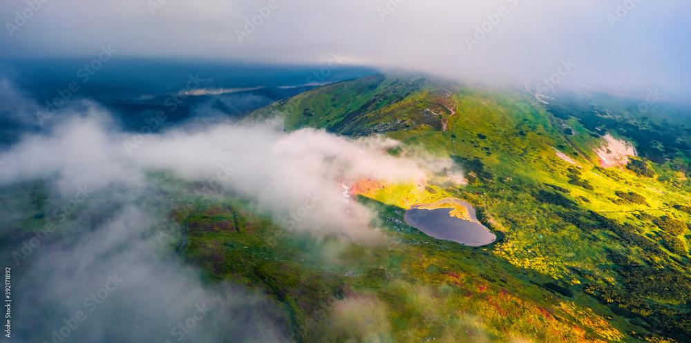 Fototapeta Panoramic view from flying drone of Nesamovyte Lake and Turkul Peak. Foggy morning scene of Carpathian mountains, Ukraine, Europe. Beauty of nature concept background..