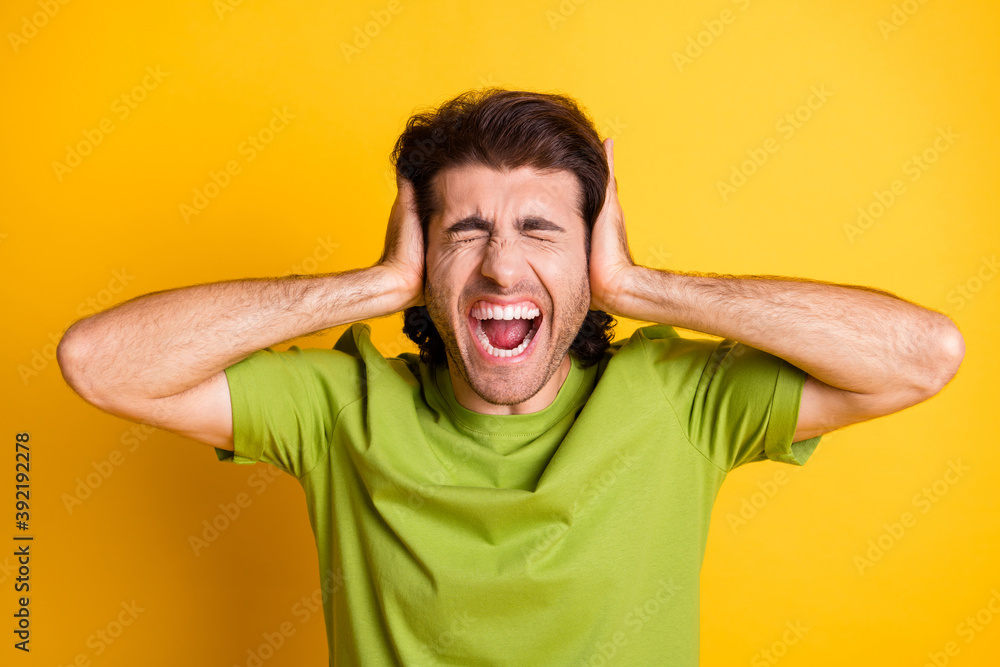 Fototapeta Photo of annoyed mad man palms cover ears open mouth closed eyes wear green t-shirt isolated yellow color background