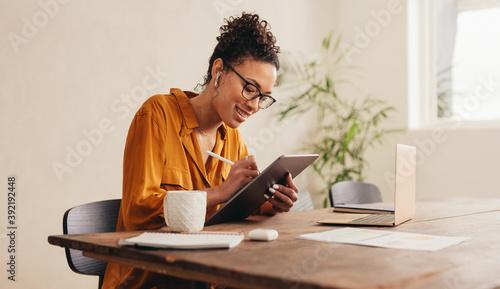 Fototapeta Female designer at home sketching on a digital tablet obraz