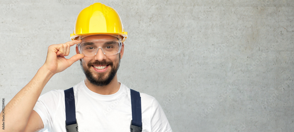 Fototapeta profession, construction and building concept - happy smiling male worker or builder in yellow helmet and overall over grey concrete background
