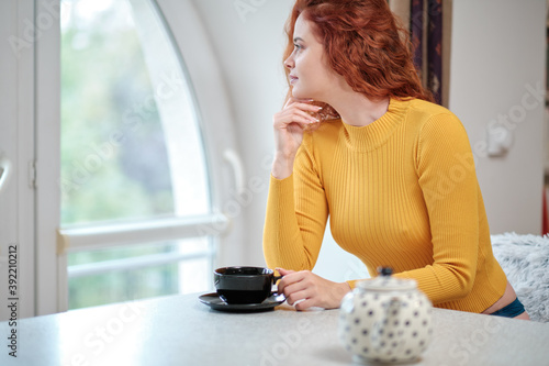 Young woman at home sipping tea from a cup