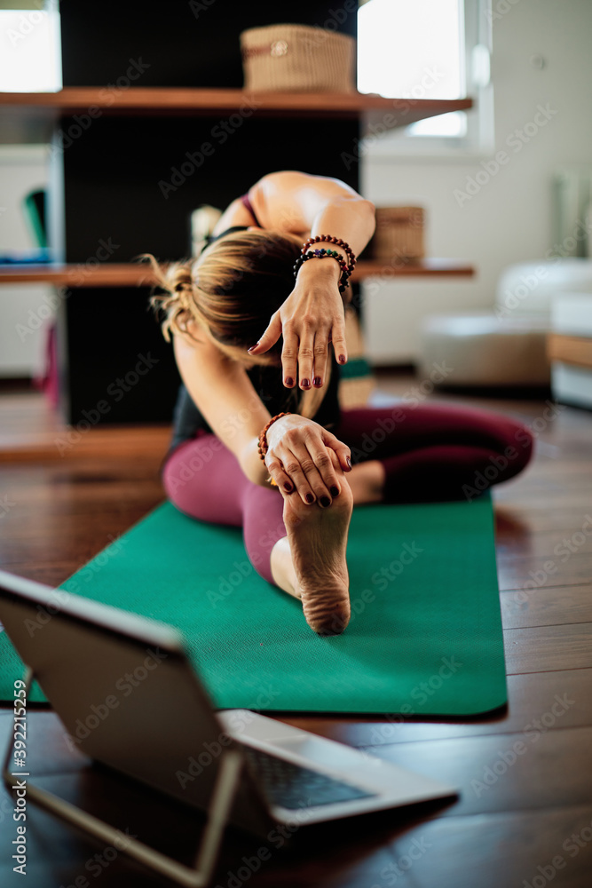 Fototapeta Middle-aged flexible woman sitting at home in head to knee yoga posture and following instruction over laptop.