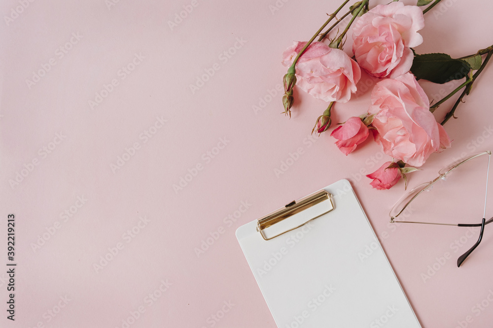 Fototapeta Blank paper sheet clipboard note pad, rose flowers bouquet, glasses on pink background. Minimal home office desk table. Flat lay, top view.