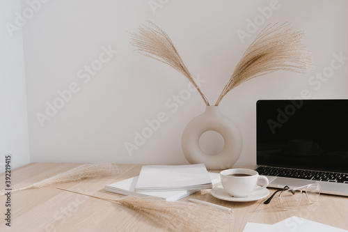 Female home office desk workspace. Blank screen laptop computer with copy space. Coffee cup, pampas grass in stylish vase, stationery on beige wooden table. Minimalist lifestyle blog mockup.