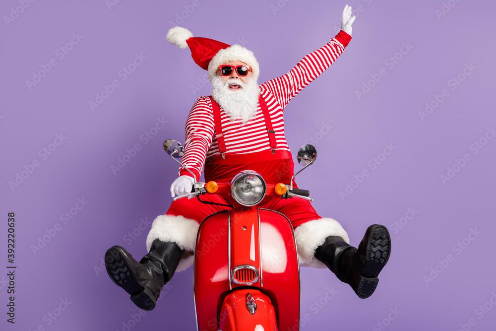 Fototapeta Photo of carefree santa claus ride retro bike wear x-mas costume striped shirt headwear sunglass isolated violet color background