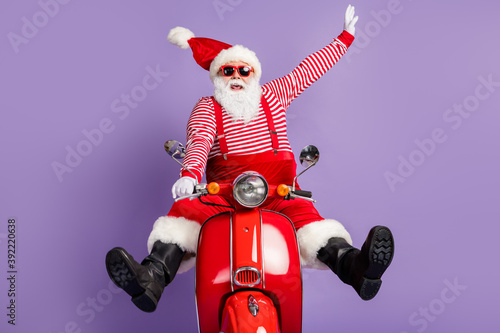 Photo of carefree santa claus ride retro bike wear x-mas costume striped shirt headwear sunglass isolated violet color background