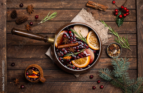 Fototapeta Christmas mulled red wine with the addition of spices and citrus fruits in a small vintage copper pan on a rustic wooden table, top view. Pot of mulled wine, traditional christmas drink. obraz