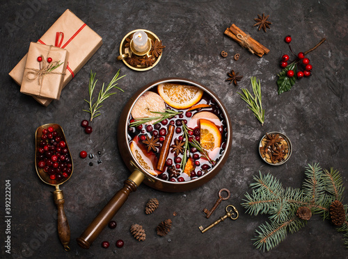 Christmas mulled red wine with the addition of spices and citrus fruits in a small vintage copper pan on a black background and gift boxes, top view. Pot of mulled wine, traditional christmas drink.