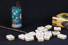 Antique Opium Pipe And Other Chinese Objects (mahjong And A Yellow Box) Against Black Background