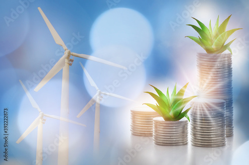 Obraz Renewable clean energy investment for sustainability  concept and alternative energy economic growth idea. Growing money plant on stack of coins and arrow with turbine and power background - fototapety do salonu