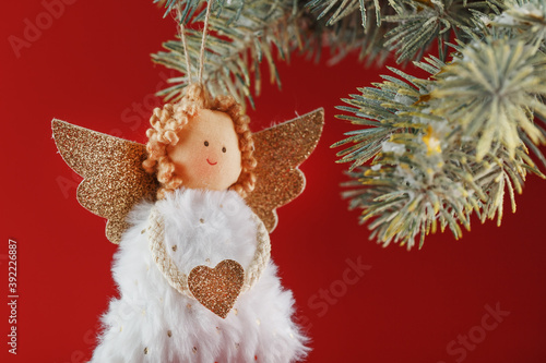 Handmade christmas angel toy on a Christmas tree on a red background Billede på lærred