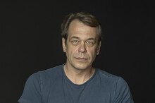 Portrait Of A Man In A Studio 40-50 Years Old In A Blue T-shirt On A Black Blurry Background, Close-up. Maybe He's Just A Buyer, An Actor Or A Truck Driver, A Loader Or A Military Pensioner
