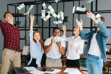 Happy Business Team Of Young Multi-ethnic Office Employees Celebrating Victory And Big Profit At Office Workplace. Cheerful Excited Young Business Man And Woman Throwing Away Banknotes.