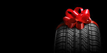 A  Black Isolation Rubber Tire, On The Grey Backgrounds In A Bow For Christmas