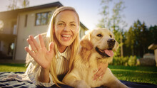 Young Beautiful Woman On Outdoors Picnic Cuddles Her Golden Retriever Pedigree Dog, Waves Hello Into Camera. Talking With Friends And Relaitves. POV Video Conference Call Concept