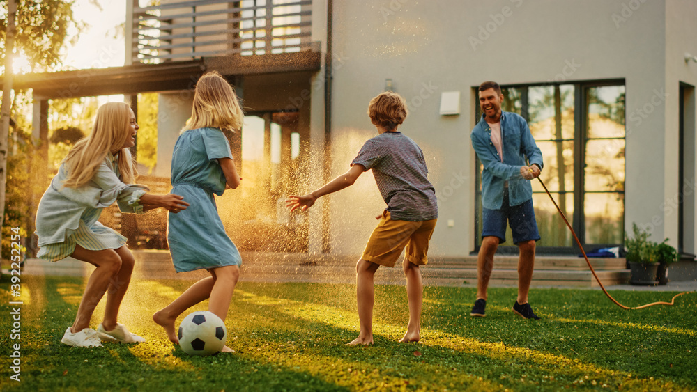 Fototapeta Happy Family of Four Playing with Garden Water Hose, Spraying Each Other. Mother, Father, Daughter and Son Have Fun Playing Games in the Backyard Lawn of Idyllic Suburban House on Sunny Summer Day