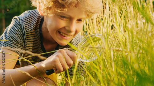 Fotografering Handsome Young Naturalist Scientist Explores Plant Life and Insect Life with Magnifying Glass