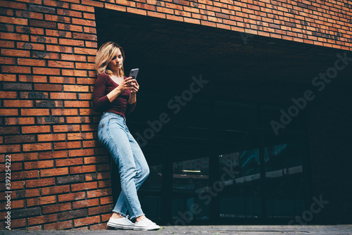 Fotografía Pretty blonde woman in stylish casual clothes surfs internet with modern smartphone in city street on sunny summer day