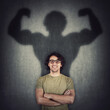 canvas print picture Confident young man shadows transforms into a muscular person on the wall as metaphor for inner strength. Motivated guy imagine flexing big biceps as super power. People self defense concept.