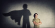 canvas print picture Confident young man keeps arms crossed smiling optimistic as casting a superhero with cape shadow on the wall. Motivated and ambitious guy tends to achieve success. Hero leadership and power concept