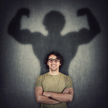 Confident Young Man Shadows Transforms Into A Muscular Person On The Wall As Metaphor For Inner Strength. Motivated Guy Imagine Flexing Big Biceps As Super Power. People Self Defense Concept.