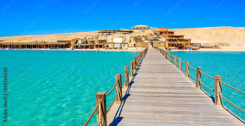 Fototapeta Wooden Pier at Orange Bay Beach with crystal clear azure water and white beach - paradise coastline of Giftun island, Mahmya, Hurghada, Red Sea, Egypt.