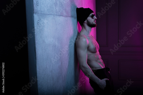 Obraz Portrait of a shirtless fit man in hat posing in dark studio with concrete wall with purple neon complementary color. - fototapety do salonu