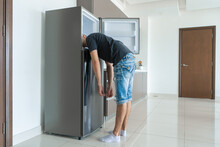On A Hot Day, The Guy Cools With His Head In The Refrigerator. Broken Air Conditioner