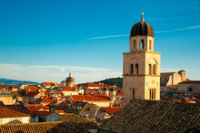 Heart Of The Old Town Of Dubrovnik, Church Belltower On The Main Street Of Stradun, Rising Above The Red Rooftops Of Many Old Small Houses. Town Famous For Its Heritage And Unesco Protection